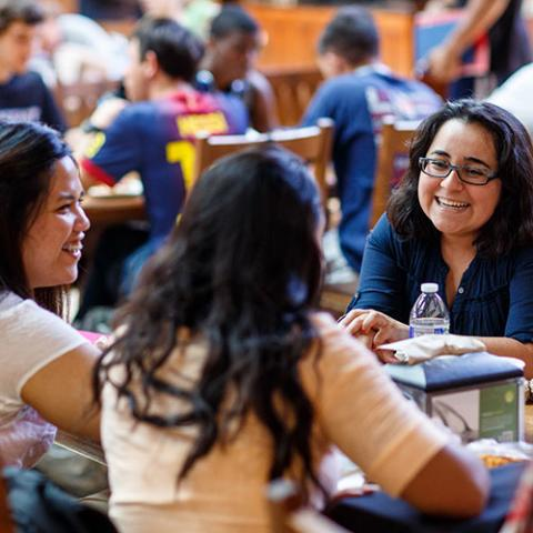 A group of students laugh and eat in Oliver Hall.