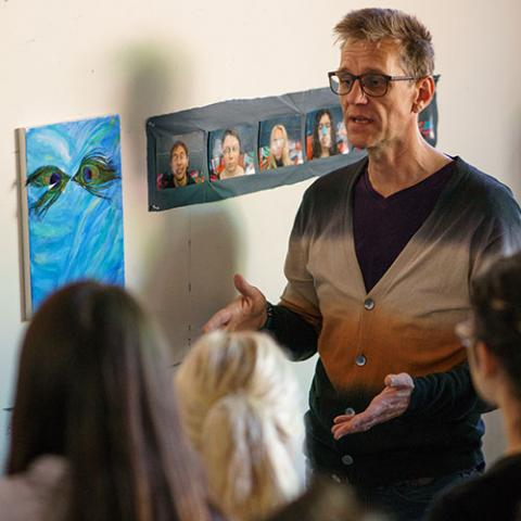 Art and Art History Professor Andrew Mount discusses a topic in front of student art work.