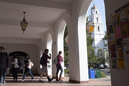 Students walk in the arcade in between classes with the Chapel in the background.
