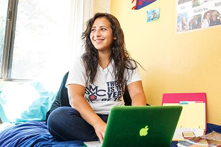 A student sits on her bed with her laptop in her residence hall.