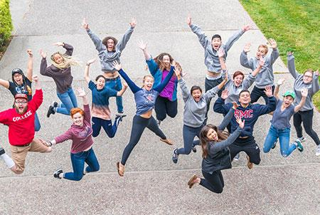 A group of Orientation Leaders jump and cheer.