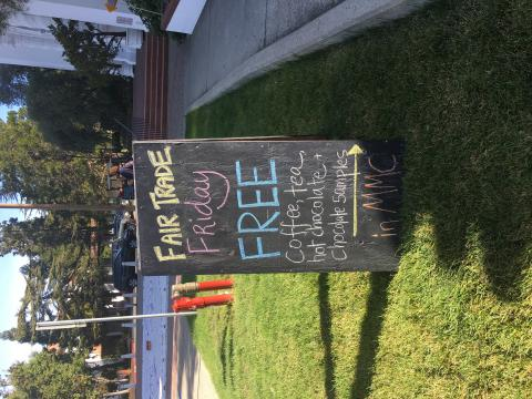 "chalkboard sign outside says ""Fair Trade Friday free coffee, tea, hot chocolate, and chocolate samples in MMC"""